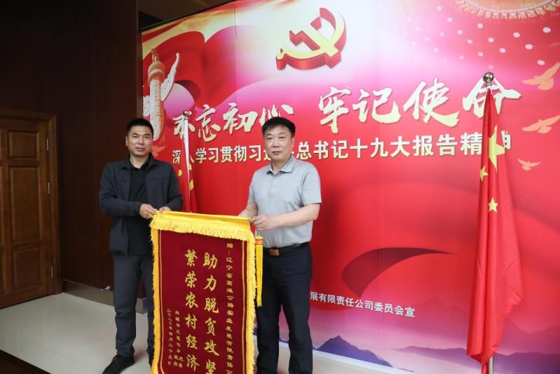 党委书记冯卫东(右)接过乡党委书记赠送的锦旗
